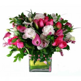Pink and White flowers arranged in a clear cubed vase.